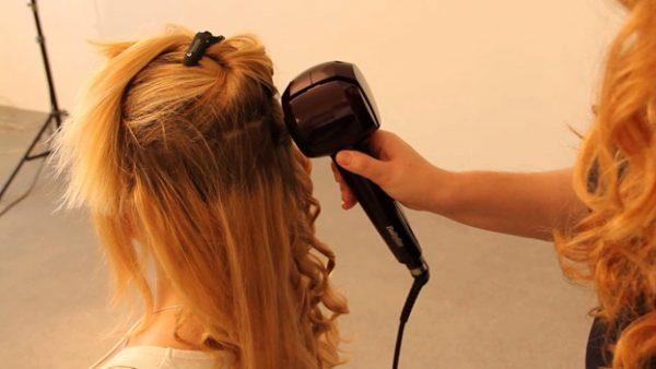 Женщине завивают волосы при помощи автоматической плойки