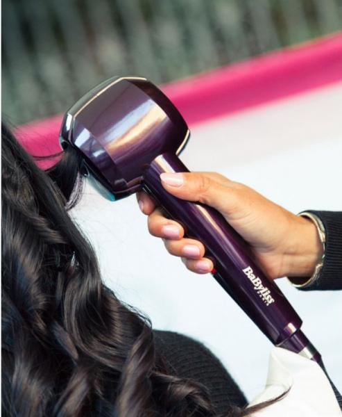 Девушке укладывают волосы при помощи автоматической плойки