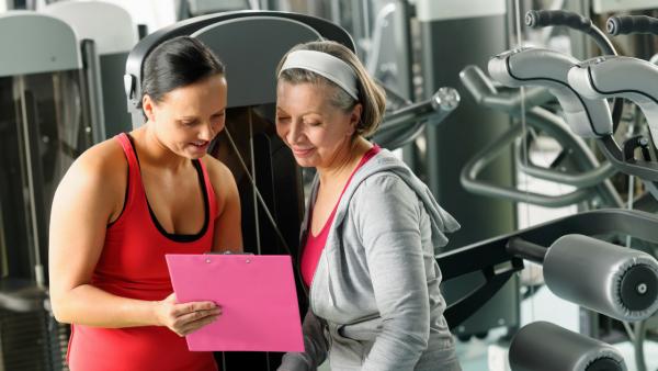 Женщина после 50 лет в спортзале с тренером