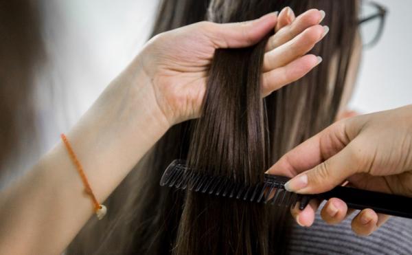 Девушке расчёсывают прядь волос