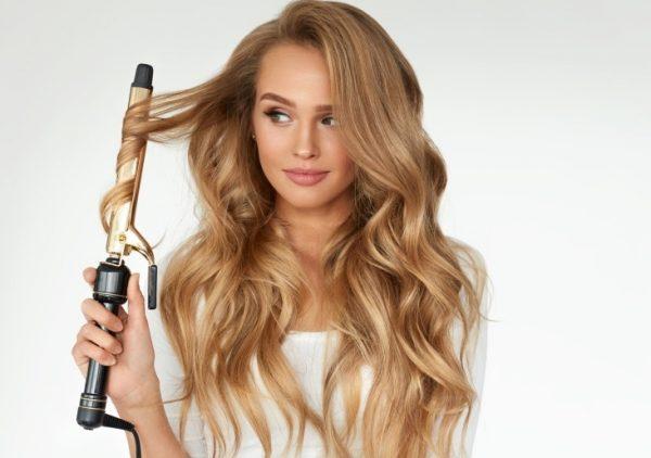 Женщина завивает длинные волосы