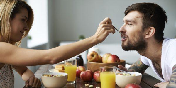 Женщина кормит мужчину овсяными хлопьями с ложки, сидя за столом