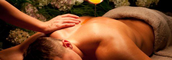 Женщина льёт масло на спину лежащего на массажной кушетке мужчине
