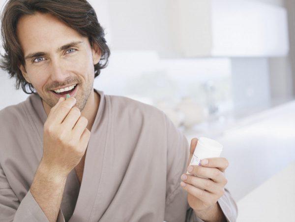 Мужчина в халате кладёт в рот таблетку