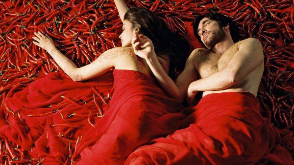 Мужчина и женщина лежат под красным покрывалом среди жгучих перцев