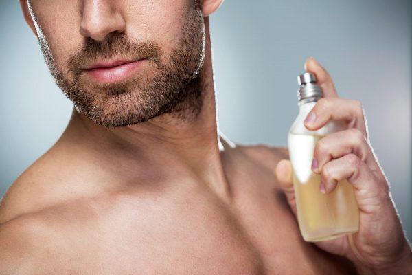 Мужчина держит в руке флакон с желтоватым парфюмом