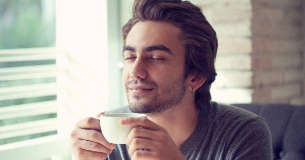 Мужчина с чашкой чая в руках сидит, закрыв глаза и улыбаясь