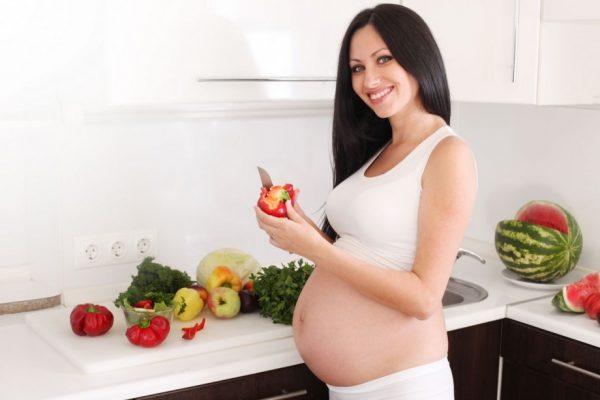 Беременная женщина с длинными волосами чистит овощи