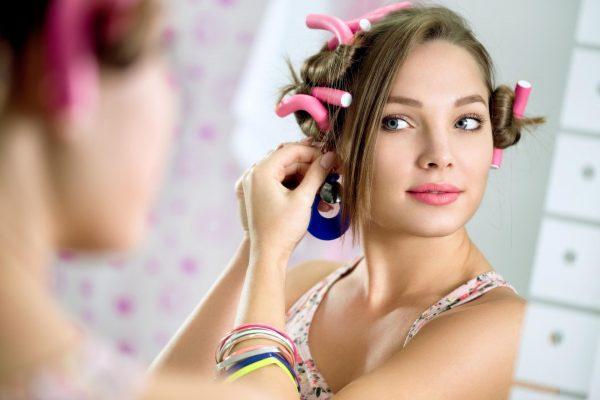 Девушка с современной моделью бигудей на голове у зеркала