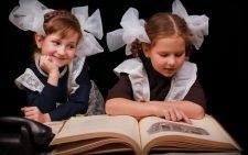 Две девочки-школьницы читают книгу