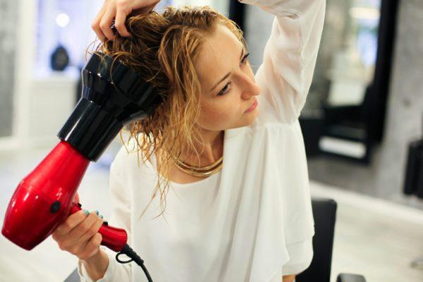 Девушка сушит голову феном