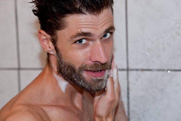 Мужчина моет бороду