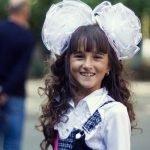 Девочка с двумя хвостиками, украшенных бантами, и челкой