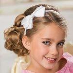 Девочка с белым ободком и бантиком-бабочкой на волосах средней длины