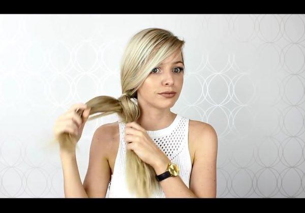Девушка протягивает одну часть волос через другую