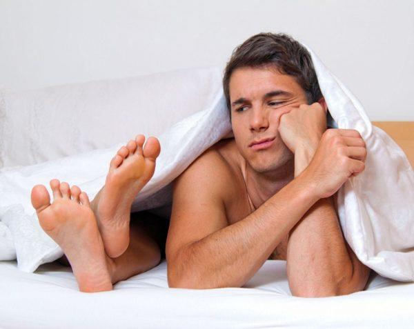 Мужчина и женские ступни, выглядывающие из-под одеяла