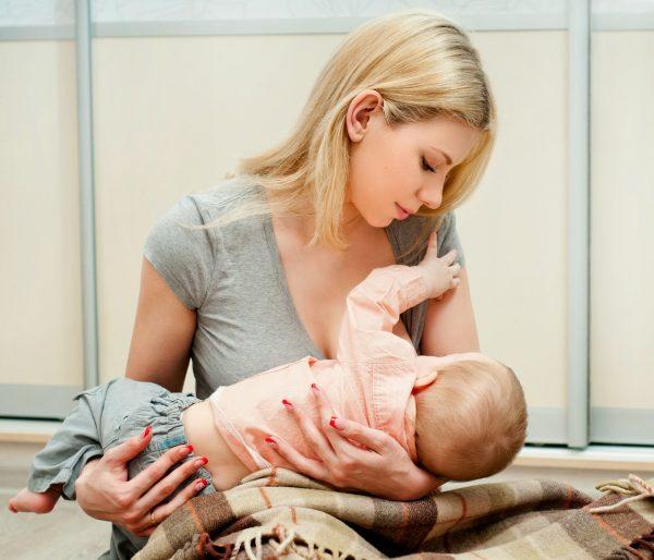 Девушка кормит малыша грудью