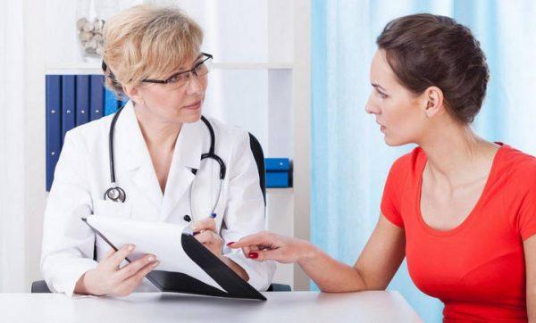 Женщина в красной футболке задаёт вопрос доктору