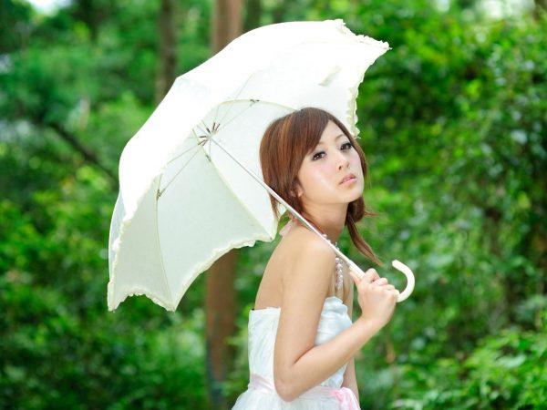 Азиатская девушка под солнцезащитным зонтиком