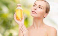 Женщина держит в руке бутылочку с жёлтым маслом и смотрит на неё