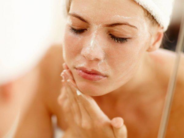 Девушка с белым полотенцем на голове наносит белую суспензию на лицо