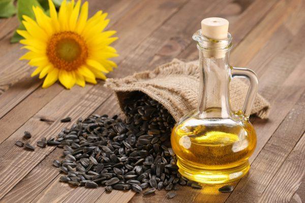 Стеклянный кувшинчик с подсолнечным маслом рядом с семенами подсолнечника в холщовом мешочке и цветком