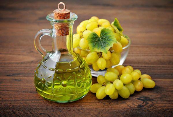 Кувшинчик с маслом и гроздья винограда в стеклянной чашке