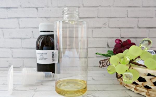 Набор для приготовления гидрофильного масла на фоне белой кирпичной стены и корзинки с фруктами