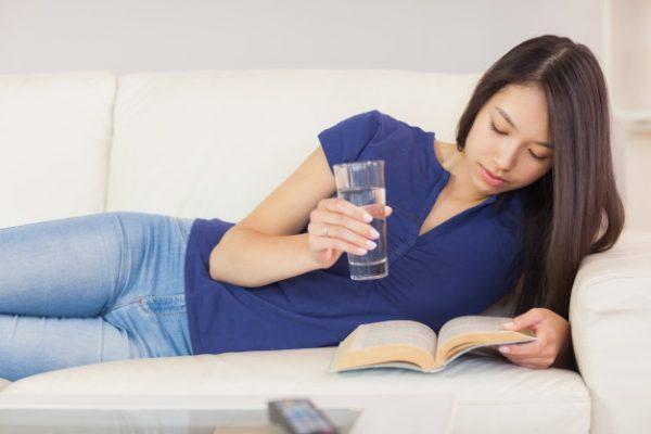 Девушка на диване со стаканом воды