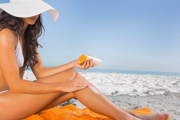 Девушка использует солнцезащитный крем