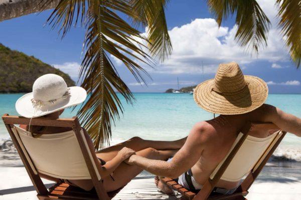 Мужчина и женщина сидят под пальмой