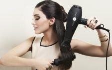 Девушка укладывает свои длинные волосы феном