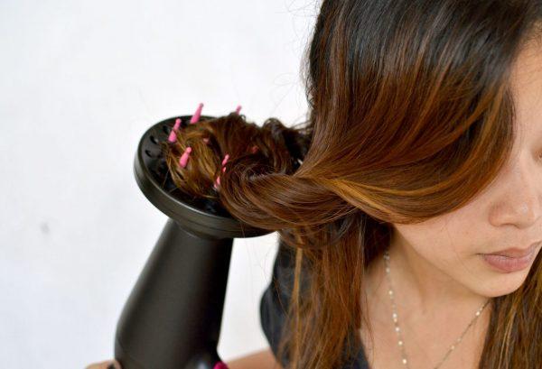 Девушка сушит прядь волос феном с диффузором