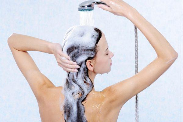 Девушка смывает с волос шампунь