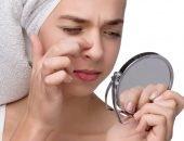 Девушка рассматривает свой нос в зеркале