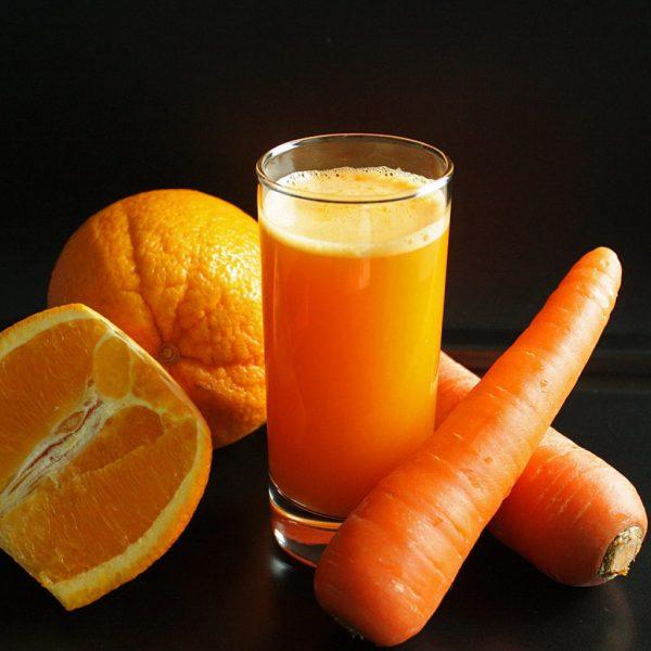 Морковь, апельсин в разрезе и сок в стакане