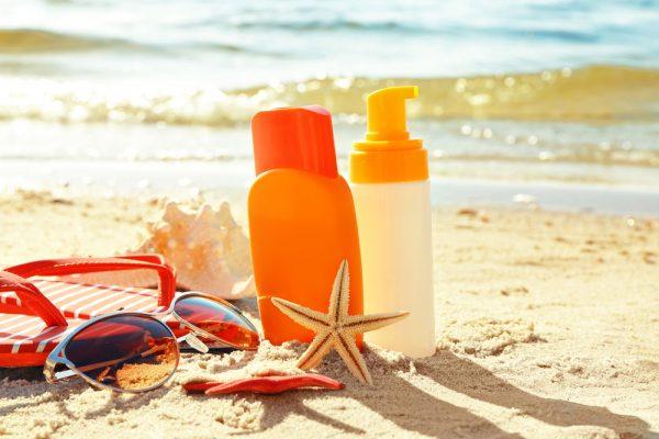 Флаконы со средствами для ухода за кожей на пляже