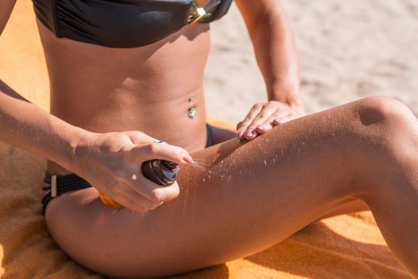 Нанесение масла для загара на кожу