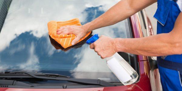 Мужчина моет стекло автомобиля специальной жидкостью