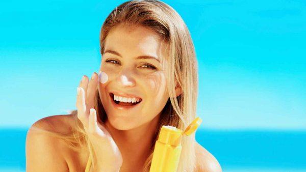 Девушка наносит на лицо солнцезащитный крем