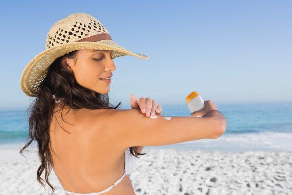 Девушка использует солнцезащитное средство