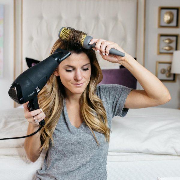 Девушка укладывает волосы феном
