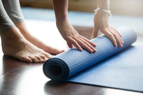 Девушка расстилает коврик для йоги