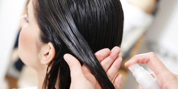 Мастер наносит на волосы девушки закрепляющий состав
