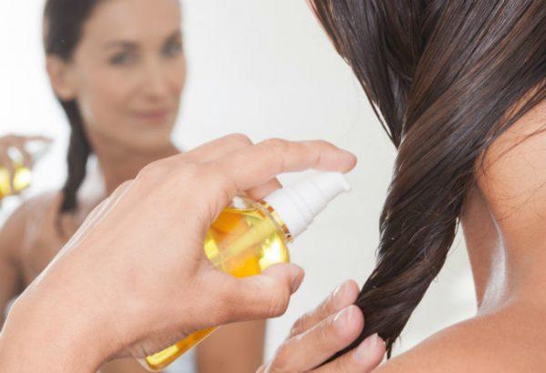 Девушка наносит закрепляющее масляное средство на волосы