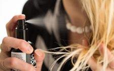 Девушка наносит средство в виде спрея на волосы